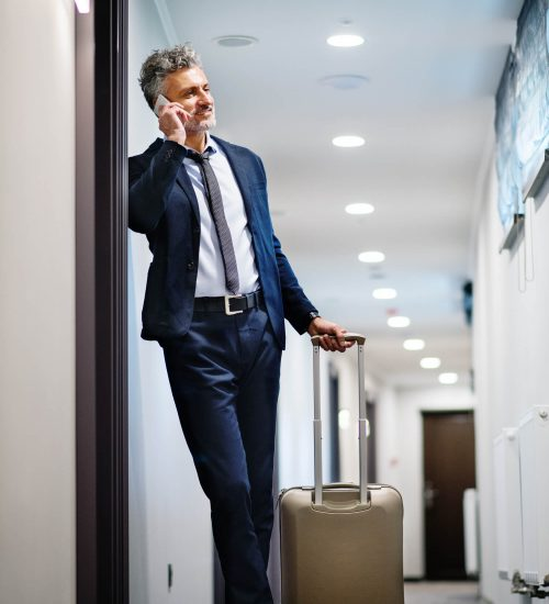 mature-businessman-with-smartphone-in-a-hotel-corr-PN53H99 (1)